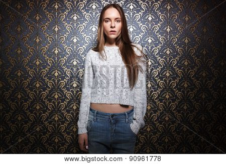 Portrait Of Young Woman Standing Against Dark Wall.