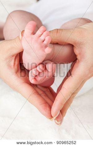Mother holding newborns feet - shallow DOF