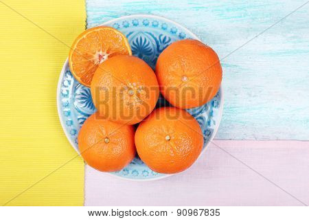 Ripe juicy tangerine on plate on wooden table top view