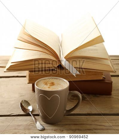Still life with cup of coffee and books on wooden table, on white background