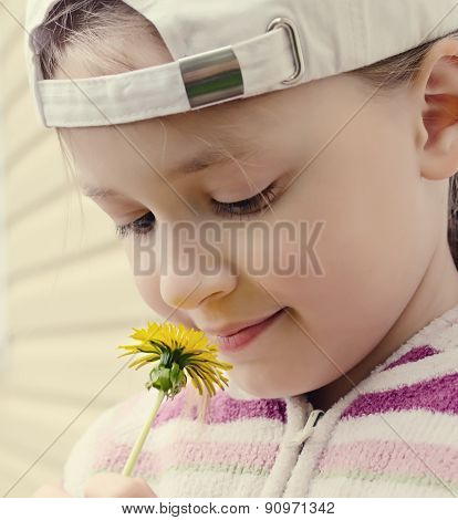 the young girl looks at a yellow flower of a dandelion
