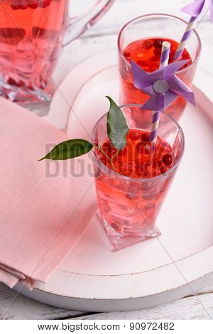 Compote with red currant in glassware on wooden tray, closeup