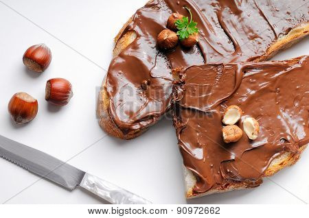 Two Slices Of Bread With Chocolate Cream And Hazelnuts