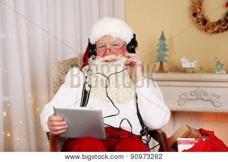 Santa Claus sitting with Digital tablet in comfortable chair near fireplace at home