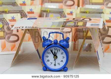 Miniature clock showing five to twelve with banknotes in the background