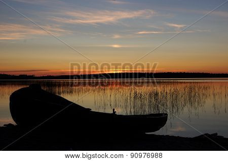 Wooden boat on the sunset lake.