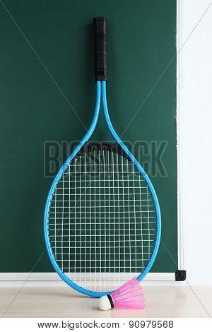 Tennis racket and shuttlecocks on blackboard background