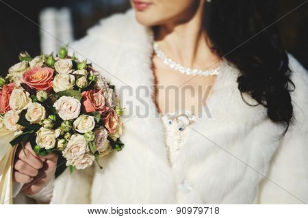 Bride In A Wedding Dress And A White Coat Holding A Beautiful Wedding Bouquet