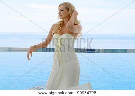 Smiling Blond Woman Wearing Strapless Sun Dress Leaning on Railing with Hands in Hair Standing on Ocean Front Resort Glass Balcony