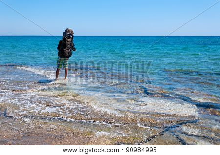Tourist with a large backpack walking through the clear water of Mediterranean Sea