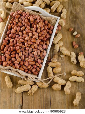 Peanuts In White Box On A Wooden Table.