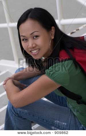Asian Student At School Sitting In Stairwell