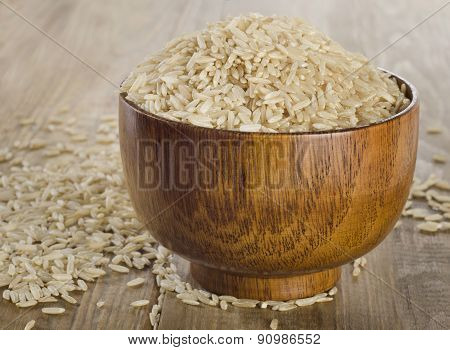 Raw Uncooked Brown Rice In A Wooden Bowl.