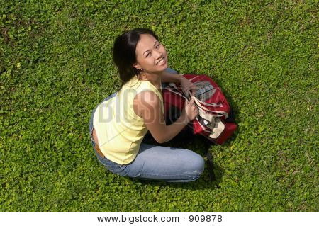 Female Student Sitting On Grass With Backpack Looking Up