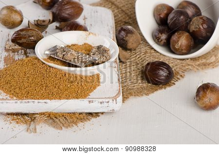 Organic Ground  Nutmeg On  A White Wooden Cutting Board.