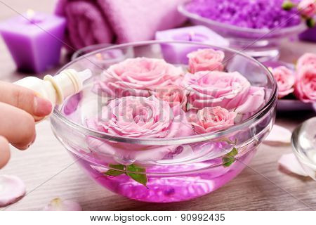 Female hand with bottle of essence and bowl of aroma spa water on wooden table, closeup