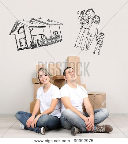 Dreaming concept. Young couple moving in new house