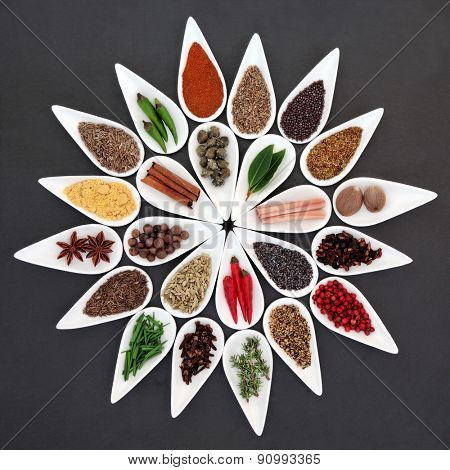 Herb and spice seasoning selection in porcelain bowls over slate background.