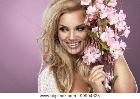 Glamorous Curvy Blonde Woman With A Sexy Body Posing With Flowers On A Pink Studio Background.