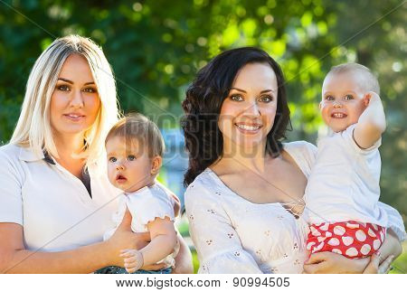 Two Happy Mothers And Their Babies
