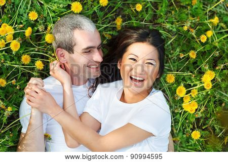 Young Loving Couple Lying At The Green Grass With Dandelion