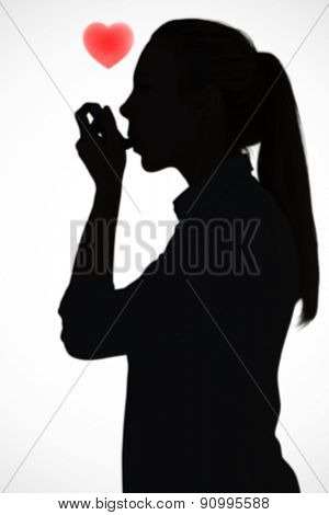 Beautiful blonde using an asthma inhaler against white background with vignette