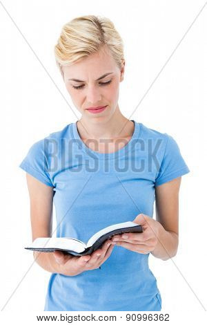 Blonde woman reading bible on white background