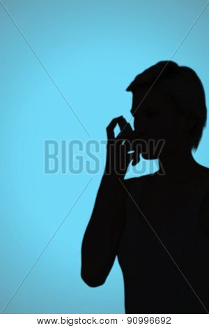 Blonde woman taking her inhaler against blue background with vignette