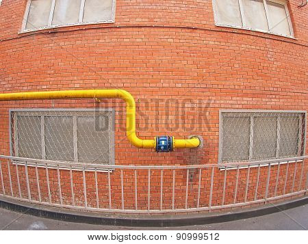 Wall Of A Building With A Gas Pipe And Windows