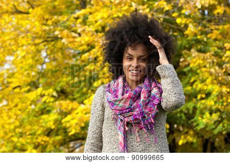 Happy Mixed Race Woman Smiling With Hand In Hair