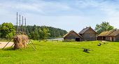 image of barn house  - Russian rural landscape with old wooden houses and barns on green meadow - JPG