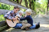 picture of guitar  - A father and his two young boy children are sitting outside on a bridge at a park playing guitar together - JPG