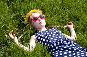 image of cheater  - young girl in beautiful summer dress sunglasses and dandelion garland lying on green grass closeup - JPG
