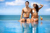 foto of couple sitting beach  - Beach couple looking - JPG
