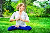 image of yoga  - Beautiful young woman doing yoga in the summer park - JPG