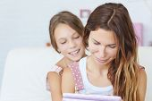 stock photo of preteens  - Mother with her preteen daugher playing ipad together - JPG