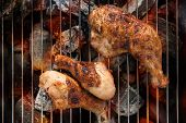 foto of thighs  - Grilled chicken thigh over flames on a barbecue - JPG