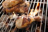 stock photo of flame-grilled  - Grilled chicken thigh over flames on a barbecue - JPG