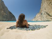 stock photo of shipwreck  - Woman relaxing on the famous Shipwreck Navagio beach in Zakynthos Greece - JPG
