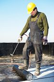 stock photo of torches  - Roofer preparing part of bitumen roofing felt roll for melting by gas heater torch flame - JPG