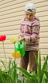 picture of red siding  - The girl of 9 years costs with a green watering can against a wall from a siding - JPG