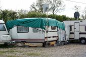 stock photo of caravan  - Travel trailer with tent and extra tarpaulin against the rain in a row of Old - JPG