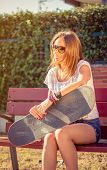 picture of sitting a bench  - Portrait of beautiful young girl with short shorts and skateboard sitting on bench in a summer day - JPG