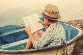stock photo of old boat  - Book Reading boy in old boat  near the lake - JPG