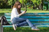 pic of sitting a bench  - Pretty young woman using smartphone sitting on bench in park at summer day - JPG