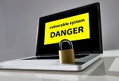 stock photo of computer hacker  - locked lock on keyboard of computer laptop with warning message on screen about danger of vulnerable system in cyber crime and hacker attack concept - JPG