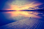 stock photo of calming  - Vintage photo of beautiful sunset over calm lake - JPG