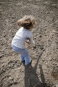 pic of hoe  - Girl digging in dry organic soil by hoe - JPG