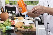 foto of hamburger  - Chef putting mayonnaise on the Hamburger bun  - JPG