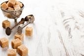 picture of tong  - Brown sugar cubes and metal sugat tongs on white wooden background - JPG